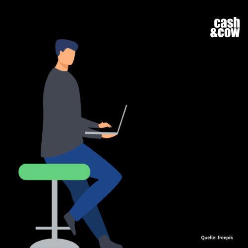 Mann sitzt auf grünem Hocker mit Laptop in der Hand